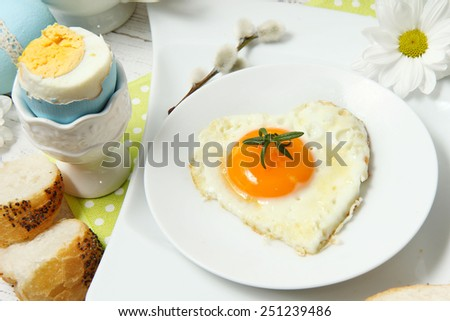 Easter table setting with flowers and eggs on old wooden table - stock photo
