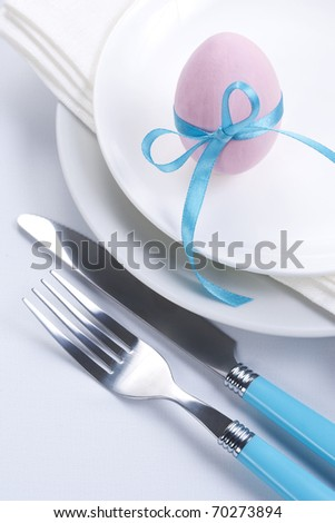 Easter table setting with plates, napkin, silverware and easter egg - stock photo