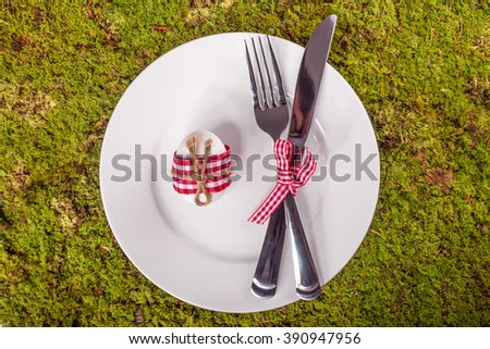 Easter table setting with white plate, knife, fork and egg on green moss background