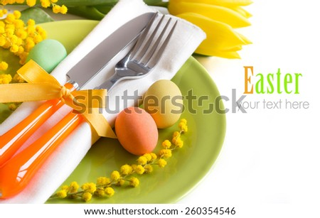 Easter table setting with yellow flowers and eggs - stock photo