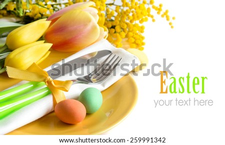 Easter table setting with yellow tulips and mimosa  - stock photo