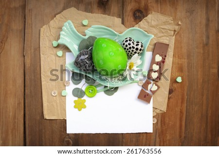 Easter themed composition with a green egg next to black and white hearts, daisy flower in a bird shaped plate over white sheet of paper, chocolates with heart shapes over white paper and brown wood  - stock photo