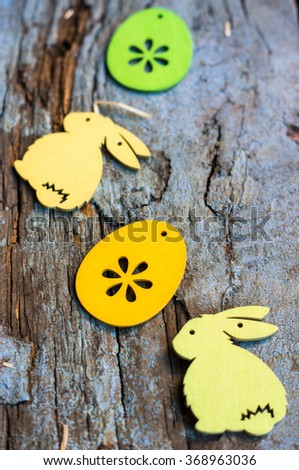 Easter time decoration with colored eggs and Easter bunny on rustic background