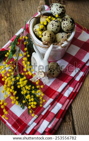 Easter time, Hand decorated Easter Eggs and speckled birds eggs in straw with a branch of colorful yellow clusters of mimosa flowers in a natural country Easter background