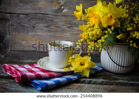 Easter time, spring flowers and cup of tea on the old wooden table - stock photo
