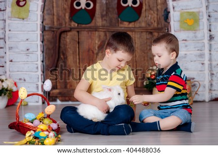 Easter, two boys with white rabbit on hands and easter eggs. - stock photo