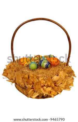 Easter wicker basket with paper covered color eggs isolated on white