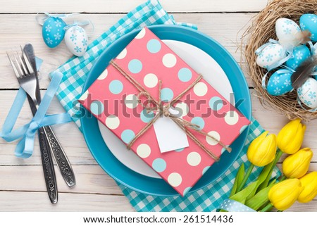 Easter with yellow tulips, colorful eggs and gift box. Top view - stock photo