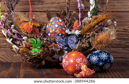 Easter wreath Easter eggs, decorative butterflies, dry grass and blooming willow on wooden background. festive composition. Easter theme. happy Easter - stock photo