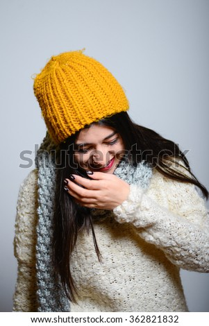 Eastern brunette girl laughs to tears, hipster in winter clothes, isolated studio portrait emotions - stock photo