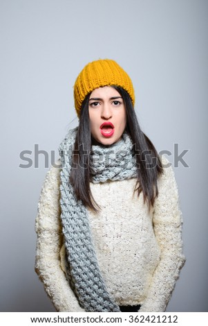 Eastern brunette girl opened her mouth in shock, hipster in winter clothing, photo studio, portrait of a woman isolated on gray background