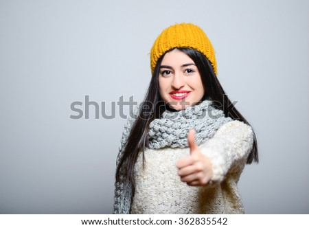 Eastern brunette girl showing thumbs up, everything is OK, hipster in winter clothes, isolated studio portrait emotions - stock photo