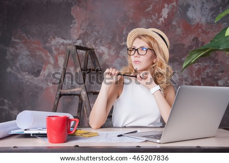 Eastern European Woman, working in CALIFORNIA, sitting in the office See the document, working on laptop computer in same time.Women working in office, working on laptop computer.