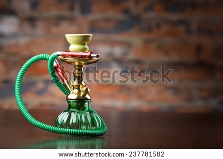 Eastern green hookah on wood table - stock photo
