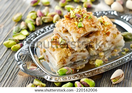 eastern traditional dessert with nuts and pistachios on wooden background - stock photo