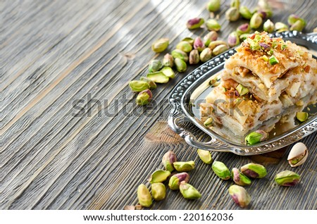eastern traditional dessert with nuts wooden sample text background - stock photo