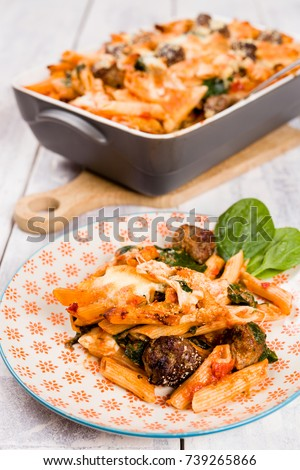 Easy one pot penne pasta oven dish with meatballs, spinach, pecorino, mozzarella cheese and tomato sauce. Served on a vintage orange plate with white wooden background. Selective focus.