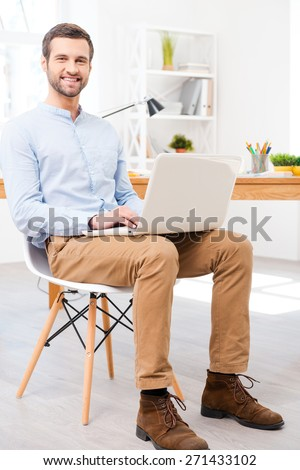 Easy to work. Handsome young man in shirt working on laptop in front of his desk and smiling at camera while sitting at office - stock photo