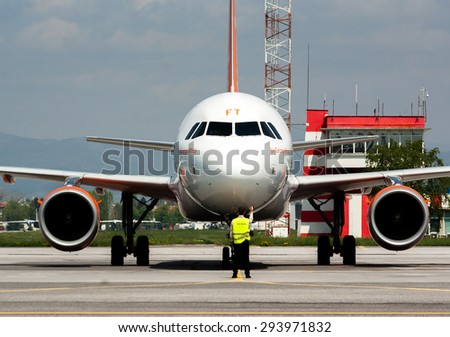 easyJet Airbus A320 has just landed at the runway of Sofia airport, Sofia, Bulgaria, April 22, 2014. Service airport worker is navigating the plane on the track. - stock photo