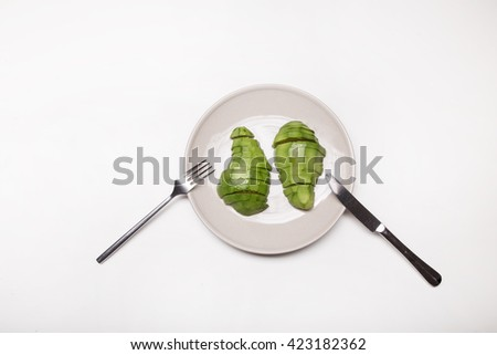 Eat avocado in a plate with knife and fork
