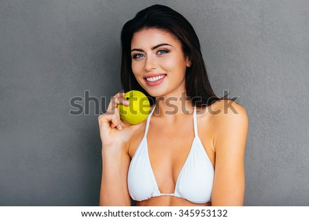 Eat healthy! Attractive young woman in white bikini holding green apple and smiling while standing against grey background - stock photo