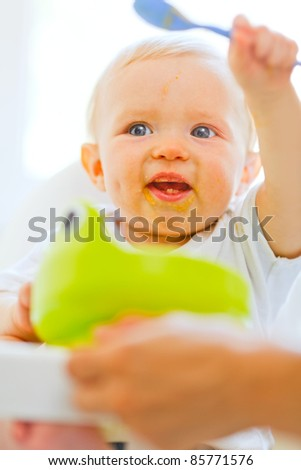 Eat smeared adorable baby  in baby chair playing with spoon - stock photo