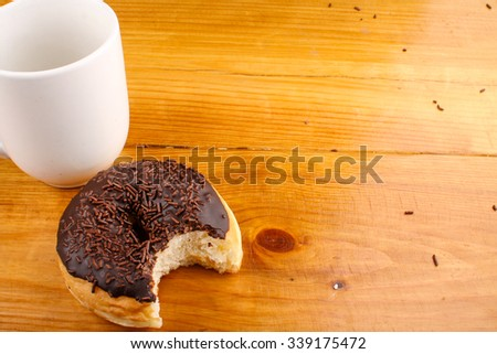 eaten chocolate doughnut with a hot drink in wood background - stock photo