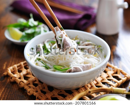 eating a bowl of pho with noodles and beef - stock photo