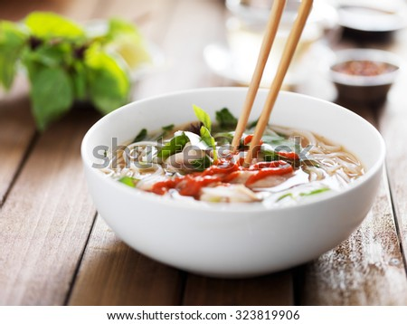 eating a bowl of vietnamese beef pho with chopsticks and spicy sriracha sauce - stock photo
