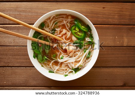 eating a bowl of vietnamese beef pho with chopsticks shot top down - stock photo