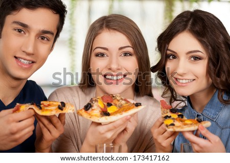 Eating a fresh pizza. Three cheerful young people eating pizza and smiling at camera