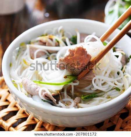 eating a steamy bowl of pho - stock photo