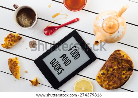 Eating and E-Reading. Egg and Cheese Sandwiches with Lemon and Honey Chamomile Tea. FOOD AND BOOKS Text Included - stock photo