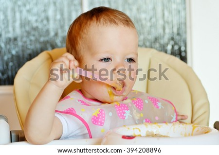 eating baby girl with spoon and dirty face