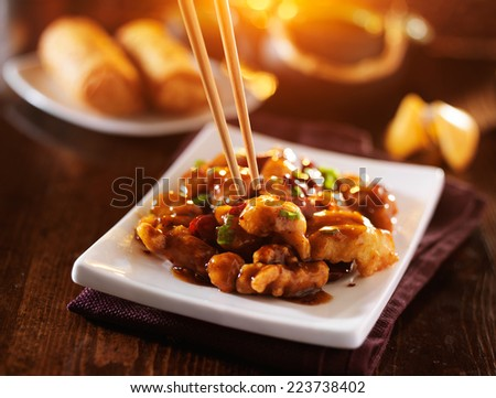 eating colorful chinese general tso's chicken with chopsticks - stock photo