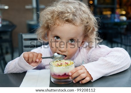 Eating Cr���¨me br���»l���©e with great enthusiasm in a coffee shop. - stock photo