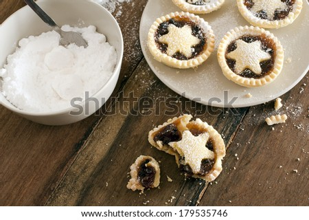 Eating delicious freshly baked Christmas mince pies decorated with pastry stars and sprinkled with icing sugar, one half eaten pie with crumbs in the foreground - stock photo