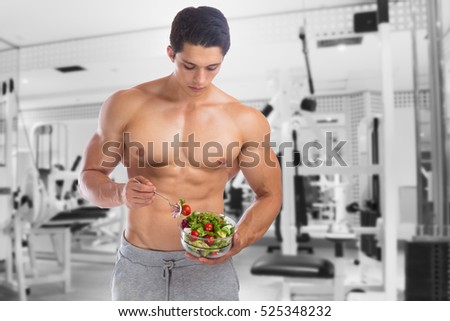 Eating food salad bodybuilding bodybuilder fitness gym body builder building muscles young man studio