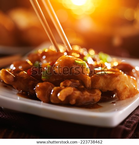eating general tso's chicken with chopsticks - stock photo