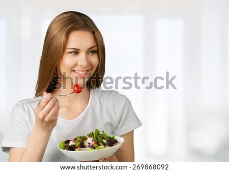 Eating. Happy young lady eating salad - stock photo