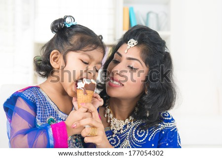 Eating ice-cream. Happy Asian India family sharing ice-cream at home. Beautiful Indian child licking ice-cream cone. - stock photo