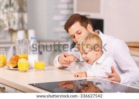 Eating it up. Father carefully feeds his small kid with milk cereal.