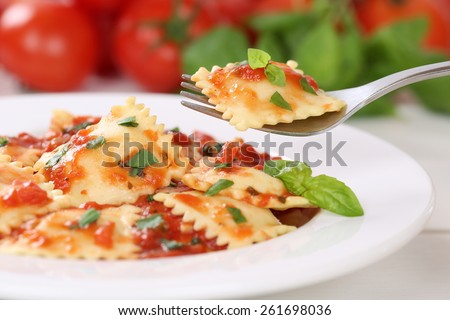 Eating Italian Pasta Ravioli with tomato sauce noodles meal with basil on a plate - stock photo