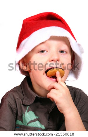 Eating My Christmas Cookie A young boy with a christmas hat on eats his cookie. Isolated over white. - stock photo