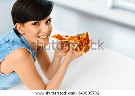 Eating Pizza. Portrait Of Attractive Caucasian Smiling Healthy Woman Eating Italian Food In Modern Kitchen At Home. Fast Food Nutrition. Diet And Lifestyle Concept.  - stock photo