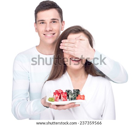 Eating sushi together. Young beautiful couple with a plate of sushi isolated on the white background. - stock photo
