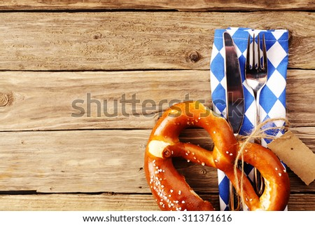 Eating utensils with a Bavarian pretzel and a white and blue napkin in Bavarian colors on a wooden table in a tavern, conceptual of Oktoberfest - stock photo