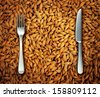 Eating wheat food as a health concept with a background of golden natural cereal grains and a place setting as a knife and fork as a diet symbol of bread and pasta or an icon of feeding the poor. - stock photo