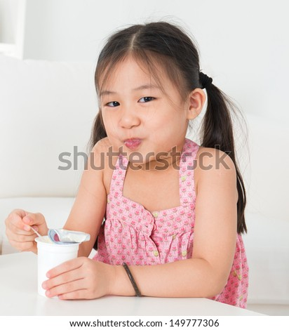 Eating yogurt. Happy Asian kid eating yoghurt at home. Beautiful child. Healthcare concept. - stock photo
