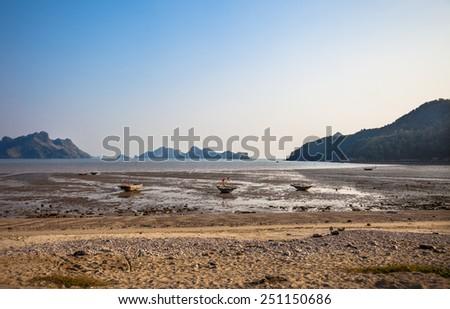 Ebb tide and small boats at Cat Ba island in Ha Long bay  - stock photo